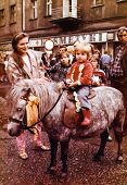 SOSNOWIEC, POLAND, AUGUST 1987 - Vintage photo of parents with their daughter posing on pony