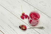 raspberry jam in a jar on wooden table