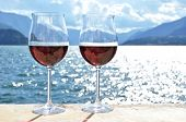 Two wineglasses against lake Como, Italy
