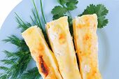 cannelloni in yellow cheese served with greenery