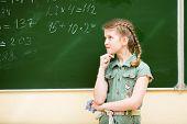 School Girl Thinking At Blackboard