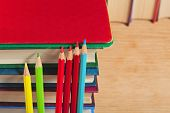 Pile Of Books And Colored Pencils On A Wooden Surface.