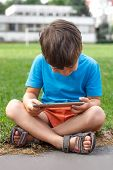 Little Boy Playing On Tablet