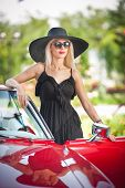 Outdoor summer portrait of stylish blonde vintage woman posing near red retro car