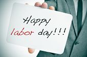 foto of labourer  - a man wearing a suit showing a signboard with the text happy labor day written in it - JPG
