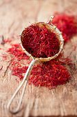 saffron spice in rustic sieve on old wooden background, closeup