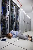 Exhausted technician sleeping on the floor in large data center