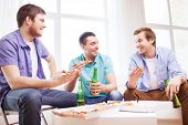 friendship, home, drinks and food concept - happy male friends with beer and pizza at home