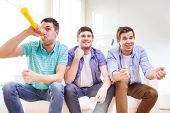 friendship, sports and entertainment concept - happy male friends with vuvuzela supporting football team at home