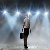 Rear view of businesswoman standing in lights of stage