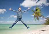 summer vacation, travel, tourism, freedom and people concept - smiling young man jumping in air over