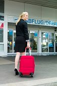 a young businesswoman with suitcase in an airport.