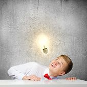 Young man looking up at electric bulb