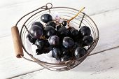 Purple grapes in basket on wooden background