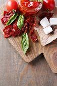 Sun dried tomatoes in glass jar, basil leaves and feta cheese on cutting board, on wooden background