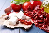 Sun dried tomatoes in glass jar, olive oil in glass bottle and feta cheese on color wooden backgroun