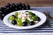 tasty salad with grape and cheese on wooden table