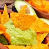closeup of a pile of nachos and guacamole