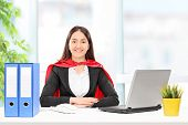Businesswoman in superhero costume sitting at a desk in an office