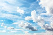 Abstract background of beautiful curly and sparse snowy white clouds like whitecaps over light brigh