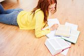 leisure, education and home concept - smiling teenage girl reading books on floor