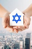 religion, judaism and charity concept - close up of woman hands holding house with star of david over city background