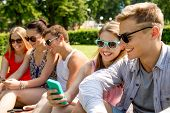 friendship, leisure, summer, technology and people concept - group of smiling friends with smartphon