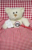 image of teddy  - Sick teddy bear lying in a red checked bed - JPG