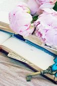 stock photo of bible story  - pile of vintage books with peony flowers and key  stacked on table - JPG