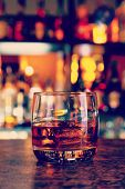 stock photo of bing  - glass of whisky on a dark wooden table with illuminated bar on the background - JPG