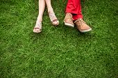 Couple Lying And Relaxing On The Grass. Legs, Top View, Text Space.