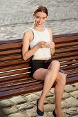 Young Woman Enjoying The Music Sitting On The Bench In Sport Wear In The City In The Morning. Rest A