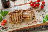 Pork Steaks Decorated With Cherry Tomatoes, Basil And Spices On Wooden Desk