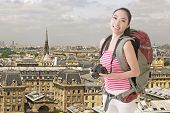 Happy smiling Asian young female backpacker with camera standing in front of skyline of Paris.