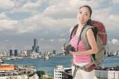 Happy smiling Asian young female backpacker with camera standing in front of Kaohsiung harbor, Taiwan, Asia.