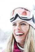 Happy woman smiling with ski googles in winter