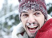 Happy smiling man with snow in his face in winter