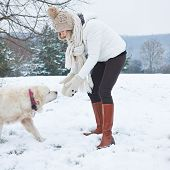 Woman walking a golden retriever dog in snowy winter