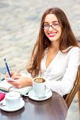 Young Woman Sitting In The Open Air Cafe With Cup Of Coffee In The Morning In The City Centre. Close