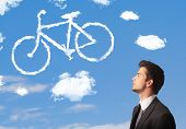Young business man looking at bicycle clouds on blue sky