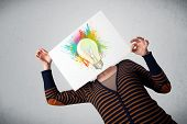 Woman holding a cardboard with coloured paint splashes and lightbulb concept in front of her head