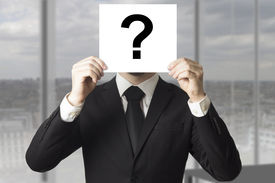 stock photo of incognito  - businessman in black suit hiding face behind sign question mark - JPG
