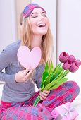 Portrait of cute excited woman with romantic letter and laughing with closed eyes, awake and surprised of gentle romantic presents on Valentine's day