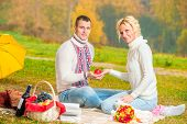 Man And Woman Hold In Their Hands A Red Apple