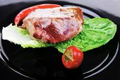 meat savory : beef grilled and garnished with green lettuce and red chili hot pepper on black dish isolated over white background