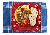 Omelet with sausage on plate and blue table mat isolated on white background