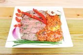 beef slice on white plate with peppers wooden table