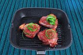 fresh grilled bloody beef steaks on black grill plate with green leaves isolated on white background