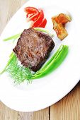 meat food : roasted fillet mignon on white plate with tomatoes apples and chili pepper over wooden table