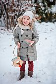 cute child girl with bird feeder and seeds in winter snowy garden